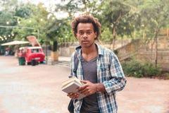 Hombre con la mochila y los libros que se colocan en el parque Fotografía de archivo libre de regalías