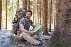 Hombre con la mochila y mapa que busca direcciones Imágenes de archivo libres de regalías