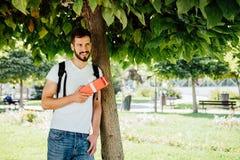 Hombre con la mochila y un regalo al lado de un árbol fotos de archivo