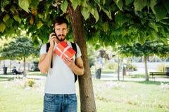Hombre con la mochila y un regalo al lado de un árbol foto de archivo