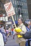 Hombre con la muestra durante maratón de la ciudad de NY Foto de archivo