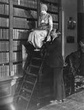 Hombre con la mujer en escalera en biblioteca (todas las personas representadas no son vivas más largo y ningún estado existe Gar Imagen de archivo libre de regalías
