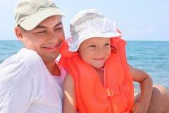 Hombre con la niña en chaleco salvavidas anaranjado en la playa fotografía de archivo