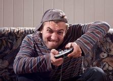 Hombre con la palanca de mando que juega a los juegos video Imagen de archivo