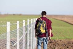 Hombre con la parte posterior al lado de la cerca de alambre Imagenes de archivo