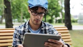 Hombre con la PC de la tableta que se sienta en el banco 10 de la calle de la ciudad metrajes
