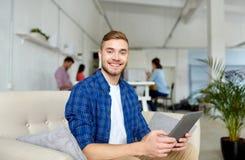 Hombre con la PC de la tableta que trabaja en la oficina fotos de archivo