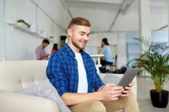 Hombre con la PC de la tableta que trabaja en la oficina imagen de archivo libre de regalías