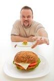 Hombre con la pequeña hamburguesa que alcanza para más grande Imagen de archivo