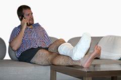 Hombre con la pierna fracturada que se sienta en Sofa Talking On Cellphone Imágenes de archivo libres de regalías