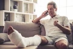 Hombre con la pierna quebrada foto de archivo