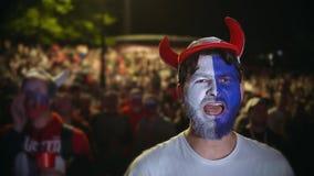 Hombre con la pintura en sus saltos de la cara en placer de la victoria del fútbol metrajes