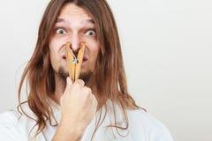 Hombre con la pinza en nariz Foto de archivo libre de regalías