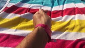 Hombre con la pulsera rosada en una mano Centro turístico u hotel Persona que toma el sol en la toalla de playa colorida LGBT irr metrajes