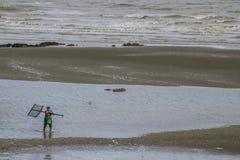 Hombre con la red del camarón en la playa durante la bajamar imagen de archivo