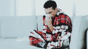 Hombre con la sentada fría en el sofá en manta a cuadros imágenes de archivo libres de regalías