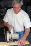 Hombre con la sierra de la habilidad Foto de archivo libre de regalías