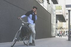 Hombre con la situación y usar de la bici el teléfono móvil foto de archivo
