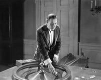 Hombre con la tabla de la ruleta Imagen de archivo libre de regalías