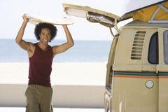 Hombre con la tabla hawaiana en autocaravana Fotos de archivo