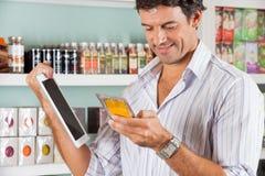 Hombre con la tableta de Digitaces que comprueba el producto en tienda imagenes de archivo