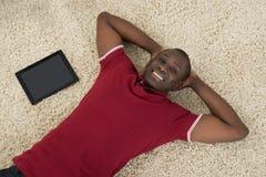 Hombre con la tableta de Digitaces que miente en la alfombra Imagenes de archivo