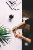 Hombre con la tableta de la tenencia del tatuaje en la tabla del escritorio de oficina con, fuentes, la flor y la taza de café Vi Foto de archivo
