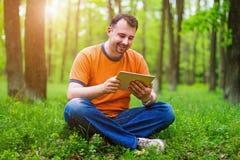 Hombre con la tableta en el parque Imágenes de archivo libres de regalías