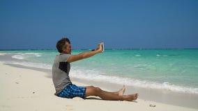 Hombre con la tableta en la playa metrajes