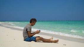 Hombre con la tableta en la playa almacen de metraje de vídeo
