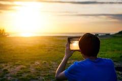 Hombre con la tableta en la puesta del sol Imágenes de archivo libres de regalías