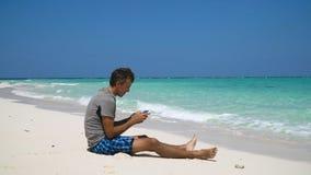 Hombre con la tableta en la playa imágenes de archivo libres de regalías