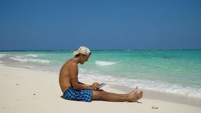 Hombre con la tableta en la playa foto de archivo libre de regalías