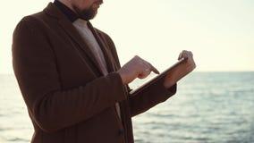 Hombre con la tableta en una playa metrajes