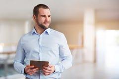 Hombre con la tableta que mira al lado en el centro de negocios imagenes de archivo