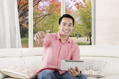 Hombre con la tableta que muestra el pulgar para arriba Imagen de archivo libre de regalías