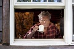 Hombre con la taza de café que mira fuera de ventana Foto de archivo