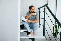 Hombre con la taza de periódico de la lectura del café en casa Fotos de archivo