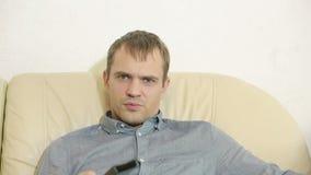 Hombre con la TV de observación teledirigida en casa metrajes