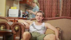 Hombre con la TV de observación teledirigida en casa almacen de metraje de vídeo