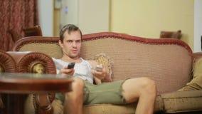 Hombre con la TV de observación teledirigida en casa almacen de video