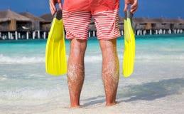 Hombre con las aletas en sus manos que se colocan en una playa maldiva Foto de archivo
