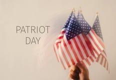 Hombre con las banderas americanas y día del patriota del texto imagenes de archivo