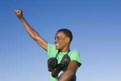 Hombre con las botas cuello redondo y brazo del fútbol aumentados contra el cielo azul Foto de archivo