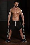 Hombre con las cadenas que muestran su cuerpo bien entrenado Fotografía de archivo