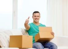 Hombre con las cajas de cartón en casa que muestran los pulgares para arriba Imagen de archivo