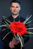 Hombre con las flores de gerberas Foto de archivo libre de regalías