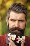 Hombre con las flores en barba Imagenes de archivo