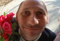 Hombre con las flores en la puerta Imágenes de archivo libres de regalías