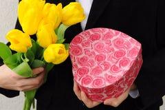 Hombre con las flores y la caja de regalo Fotografía de archivo